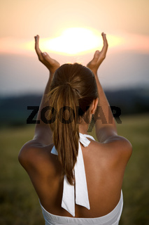 Young brunette woman in sunset