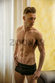 Sexy young man standing shirtless in his room