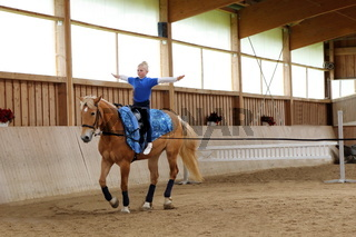 Mädchen voltigiert auf braunem Pferd