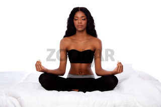 Beautiful woman sitting in lotus yoga pose on bed