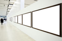 Walls in museum with empty frames and person move