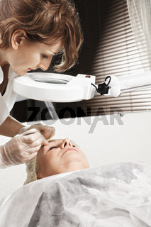 Cosmetician looking through magnifier