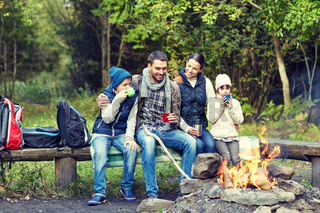 happy family sitting on bench at camp fire