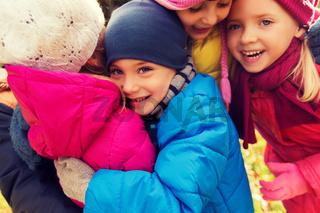 group of happy children hugging in autumn park