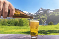 Glass of beer and summer alpine landscape