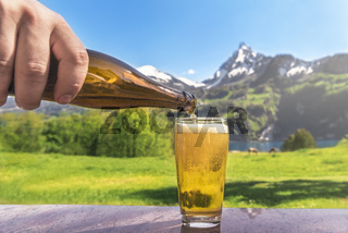 Glass of beer and summer alpine landscape