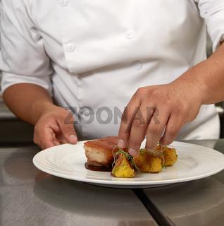 Chef Decorating Traditional Peruvian Meal Called Chicharron de Panceta de Cerdo