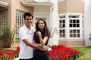 Hauskauf: Ehepaar mit Hausschlüssel vor Immobilie
