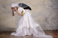 Young blond woman in wedding dress with veil and black wings in panic afraid
