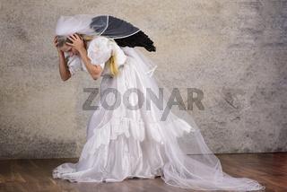 Junge blonde Frau im Brautkleid mit Schleier und schwarzen Flügeln in Panik Angst