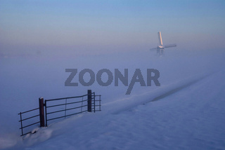 Windmill in a misty and wintry landscape