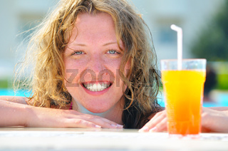 close up of pretty woman in swimming pool with cocktail