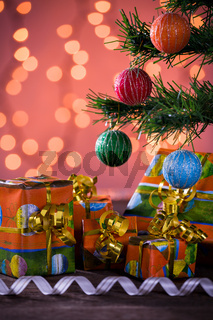 Christmas gifts with blurred lights and ribbon under the tree