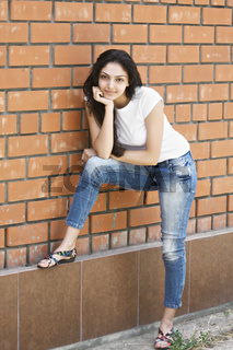 Young brunette standing at wall