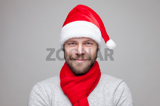 Portrait of a handsome man with beard wearing a Christmas hat