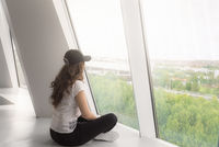 Girl sitting on floor and looking on the window