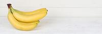 Bananen Frucht Früchte Banner Textfreiraum auf Holzplatte