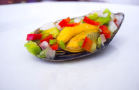 Saltwater mussel shell seasoned with raw chopped vegetables or Mussel vinaigrette
