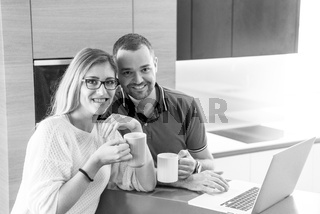 couple drinking coffee and using laptop at home