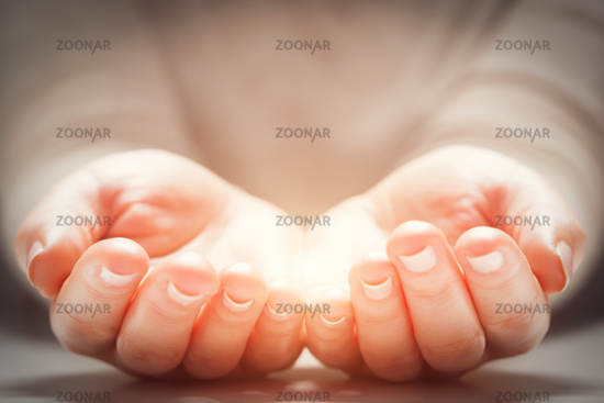 Light in woman#39;s hands. Concepts of sharing, giving, new life