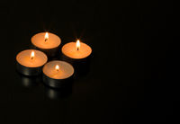 Four burning candles with reflection