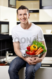 The young happy man holds capacity with vegetables