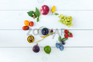 Fitness healthy food on white wooden background (lime, strawberry, plum, figs, raspberries, grapes, peppers, peaches, tomatoes nectarines and measuring tape)