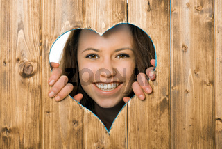 Junge Frau sieht durch ein Herz