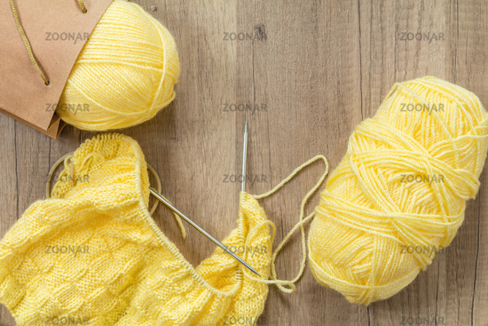 Light yellow knitting wool and knitting needles on wooden background
