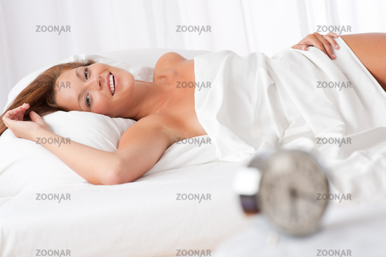 White lounge - Smiling woman lying in white bed