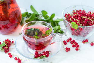 Redcurrant drink in transparent glass carafe and cup. Clear glass vase with red currant berries on the white wooden background.