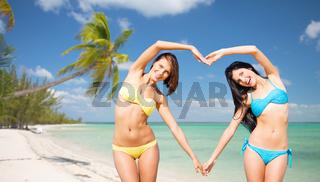 happy women making heart shape on summer beach