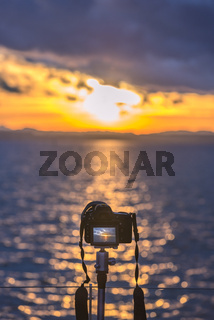 Camera on a tripod capturing the sunset