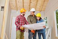 Handwerker planen in Teamwork die Sanierung