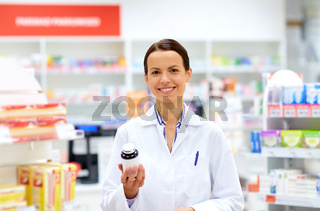 happy female apothecary with drug at pharmacy