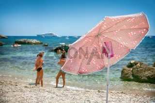 The Umbrella on a pebble beach in the background with people