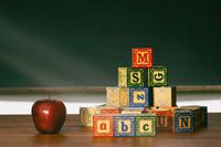 Wooden blocks and apple on desk