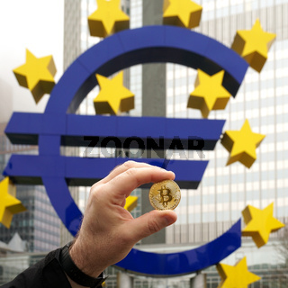 hand holding a Bitcoin coin next to the Euro sign in Frankfurt Germany