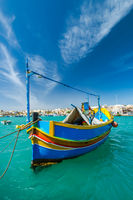 Beautiful painted fishing boat on turquoise water in Marsaxlokk,Malta