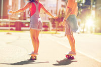 teenage couple riding skateboards on city street