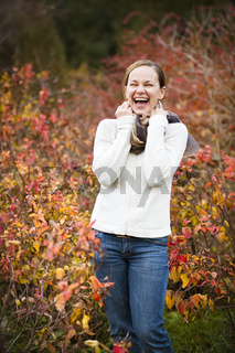Young pretty smiling woman in autumn forest