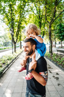 little girl riding on dads neck