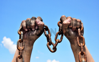 Two male hands holding a rusty metal chain