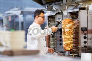 chef slicing doner meat from spit at kebab shop