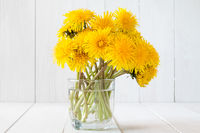 Dandelion flowers in glass with water