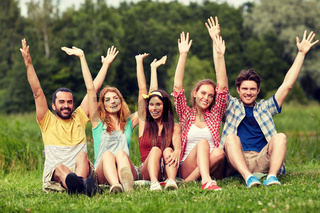 group of smiling friends waving hands outdoors