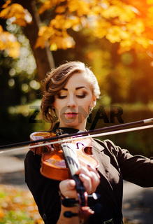 Portrait of smart girl with violin on hands outdoor in brown coat on autumn.