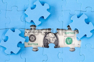 USD banknote hidden under puzzle