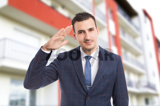 Polite real estate manager on new apartment building background