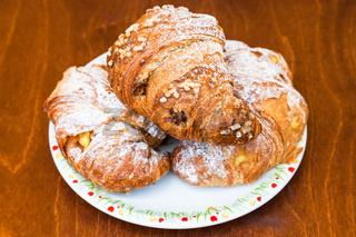 three fresh croissants on table